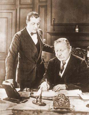Der berühmte englische Schriftsteller Conan Doyle der berühmte Veter der bekannten Cherlock-Holmes-Romane ist, 71 Jahre alt, in London gestorben.Unser Bild zeigt den berühmten englischen Schriftsteller Conan Doyle bei der Arbeit an seinem Schreibtisch. Stehend sein Sohn Adrian Doyle.